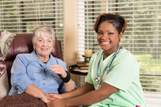 Caring home healthcare nurse helps caucasian senior adult woman at her home or an assisted living facility.  The female patient is sitting in her comfortable recliner while her African descent nurse or doctor provides assistance. Home windows in background.