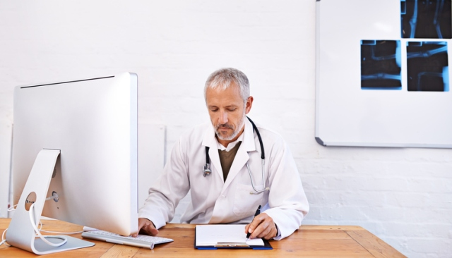 Shot of a mature male doctor working at a desktop computer in his office