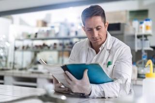 Mid adult male scientist reading scientific data in a laboratory.